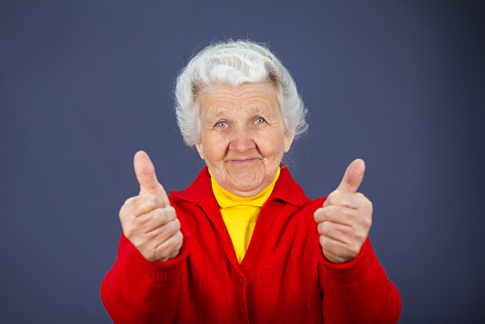 Closeup portrait senior, mature, happy, smiling excited natural woman giving thumbs up sign with fingers, isolated blue background. Positive emotions, facial expressions, symbols, feelings, attitude-1